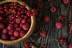 Fresh berries on wooden table. Fresh berries raspberry and red currant in bowl on wooden table Royalty Free Stock Photo