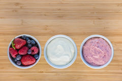 Fresh berries with yoghurt and ice-cream. On wooden board Stock Photo