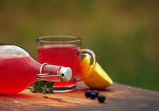 Fresh berry compote in a glass mug, lemon and a bottle on a wooden surface Stock Images