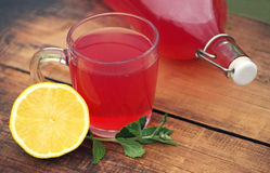 Fresh berry compote in a glass mug, lemon and a bottle on a wooden surface Royalty Free Stock Photo