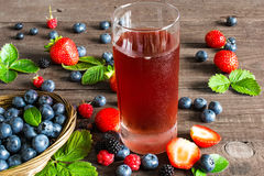 Fresh berry drink with strawberries, blueberries, blackberries and raspberries. In a glass with ripe berries on wooden table Royalty Free Stock Photography