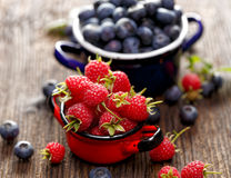 Fresh berry fruits in a enameled pots. Fresh raspberries and blueberries in a enameled pots on a wooden rustic table Royalty Free Stock Photos