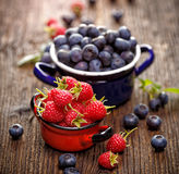 Fresh berry fruits in a enameled pots. Fresh raspberries and blueberries in a enameled pots on a wooden rustic table Stock Image