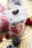 Fresh berry fruits frozen in ice cubes Royalty Free Stock Photos