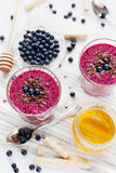 Fresh berry smoothie, milkshake, yogurt, dessert decorated grated chocolate, honey and blueberry Royalty Free Stock Image