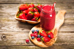 Fresh berry smoothie. Fresh red berry smoothie on wooden table Stock Images