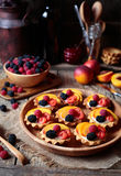 Fresh berry tartlet or cake with vanilla custard, raspberry, peach and blackberry. Rustic style. Close up. Stock Photo