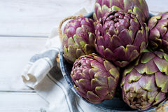 Fresh big Romanesco artichokes green-purple flower heads ready t. O cook seasonal food Royalty Free Stock Photo