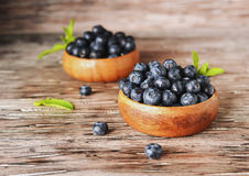 Fresh bilberries or blueberries in small wooden bowls, selective focus. Fresh bilberries or blueberries in small wooden bowls on a rustic table, selective focus Royalty Free Stock Image