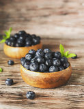 Fresh bilberries or blueberries in small wooden bowls, selective focus. Fresh bilberries or blueberries in small wooden bowls on a rustic table, selective focus Stock Image