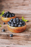 Fresh bilberries or blueberries in small wooden bowls, selective focus. Fresh bilberries or blueberries in small wooden bowls on a rustic table, selective focus Royalty Free Stock Photography