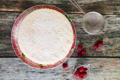 Fresh biscuit cake with raspberry yoghurt cream. Sprinkled with powdered sugar and fresh raspberries on wooden background Royalty Free Stock Image