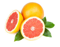 Fresh bitter juicy grapefruit halves. With green leafs. Isolated on white background royalty free stock images