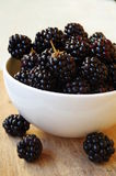 Fresh black blackberries in a white cup. On wooden background Stock Photo