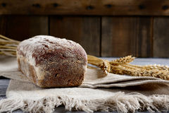 Fresh black bread with wheat spikelets on a wooden background. Concept of harvest stock image