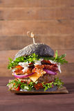 Fresh black burger with beef, cheese, salad, pickles, tomatoes, red onion and bacon on wood background Stock Photography