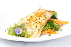 Fresh black cod on bed of broccoli and carrots Royalty Free Stock Image