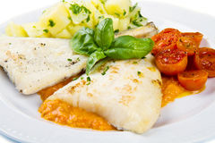 Fresh black cod with potatoes and tomatoes sauce Stock Photo