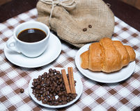 Fresh black coffee with beans and croissant on tablecloth. Cup of fresh black coffee with beans and croissant on tablecloth Royalty Free Stock Photos