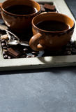 Fresh black coffee in a cups and chocolate and black background Stock Photography