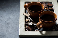 Fresh black coffee in a cups and chocolate on blackboard Stock Photos