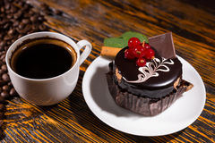Fresh black coffee in mug by chocolate cupcake. Fresh black coffee in mug by pile of beans and chocolate cupcake dessert on white plate decorated with red Royalty Free Stock Images