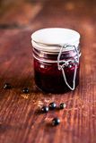 Fresh black currant, blackberry and black raspberry jam or marmalade in a jar on a wooden table Stock Image