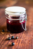 Fresh black currant, blackberry and black raspberry jam or marmalade in a jar on a wooden table Stock Images