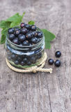 Fresh black currant in the glass, on rustic wooden board. Royalty Free Stock Image