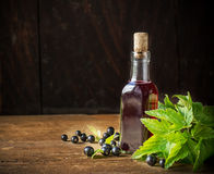 Fresh Black Currant juice with some fruits. Fresh Black Currant juice in a glass bottle with branches and berries currants on a dark wooden background. selective Stock Photos