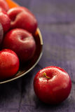 Fresh Black Diamond plums from Portugal in a copper bowl on a blue silk background with copy space. Selective focus. Close up. Bac Royalty Free Stock Photo