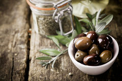 Fresh black olives and herbs. A bowl of fresh black olives and container of dried herbs stand on an old wooden kitchen table for use as ingredients in cooking stock images