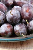 Fresh black plums. On table, close-up Royalty Free Stock Photos