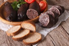 Fresh black pudding with tomato close-up. horizontal Stock Image