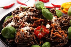 Fresh black tagliolini pasta. Fresh homemade pasta with basil and tomato on the rustic table royalty free stock image
