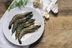 Fresh black tiger shrimps on a plate on a rustic wooden board, g Royalty Free Stock Images
