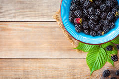 Fresh blackberries in blue ceramic bowl and leaves on wooden background in rustic style. Top view Stock Photography
