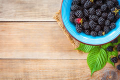 Fresh blackberries in blue ceramic bowl and leaves on wooden background in rustic style. Top view Royalty Free Stock Photos