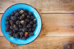 Fresh blackberries in blue ceramic bowl on wooden background in rustic style. Top view Stock Photography