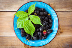 Fresh blackberries with leaves in blue ceramic bowl on wooden background in rustic style. Top view Royalty Free Stock Photography