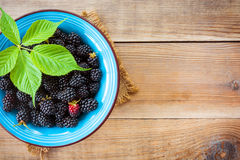 Fresh blackberries with leaves in blue ceramic bowl on wooden background in rustic style. Top view Stock Photos