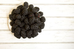 Fresh blackberries on white china plate. Close up of fresh blackberries on white china plate stock image
