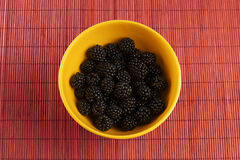 Fresh blackberries in a yellow bowl. With brown tablecloth Stock Photos