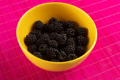 Fresh blackberries in a yellow bowl. With pink tablecloth Royalty Free Stock Photos