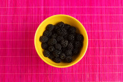 Fresh blackberries in a yellow bowl. On the table Royalty Free Stock Image