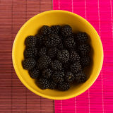 Fresh blackberries in a yellow bowl. With two different tableclothes Stock Photo
