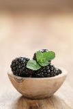 Fresh blackberry with mint leaves in wooden bowl on table closeup Royalty Free Stock Photo