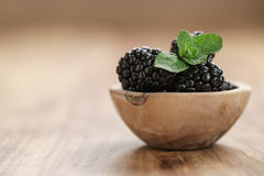 Fresh blackberry with mint leaves in wooden bowl on table closeup Stock Photography