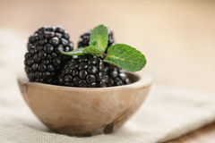 Fresh blackberry with mint leaves in wooden bowl on table closeup Royalty Free Stock Image