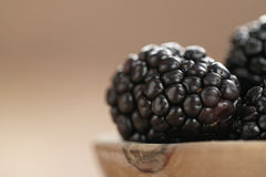 Fresh blackberry in wooden bowl on table closeup Stock Images